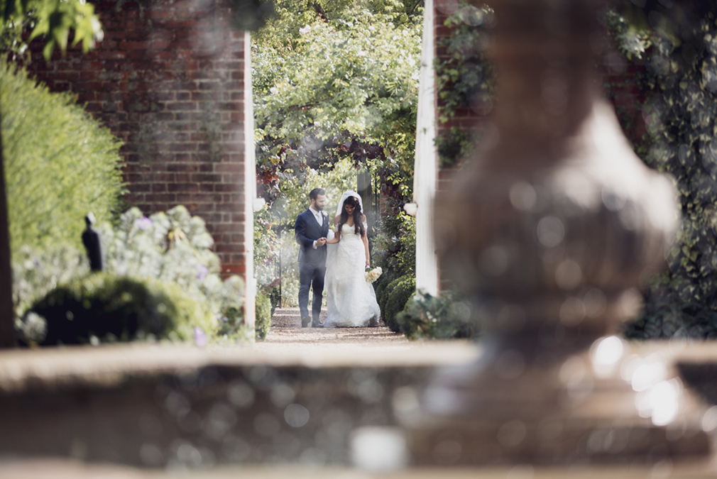 A bride and groom take some time to explore the gardens at Braxted Park