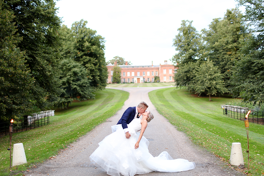 A bride and groom share a kiss at the top of the sweeping driveway at Braxted Park on their wedding day