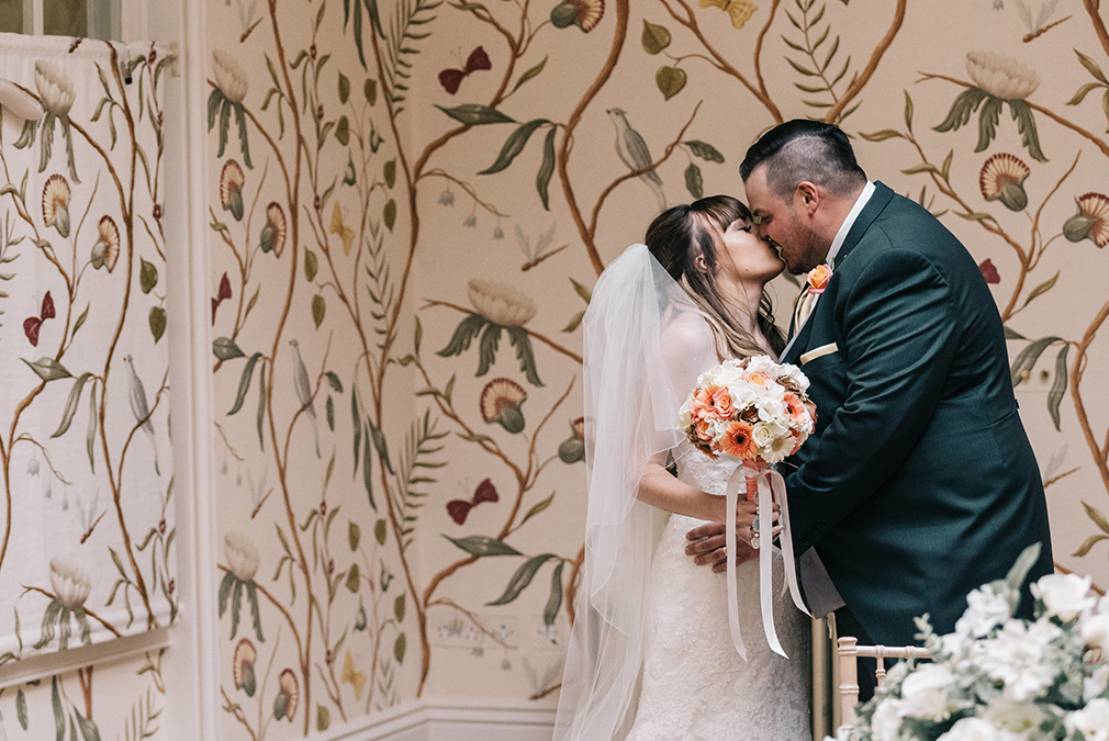 The bride and groom share a kiss after their summer wedding ceremony at Braxted Park