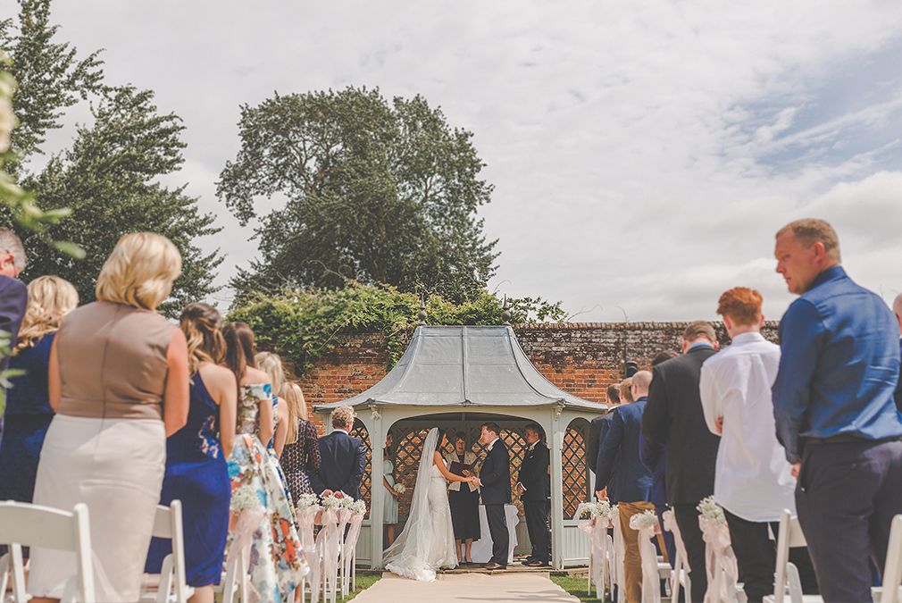 The bride and groom say their vows during an outdoor wedding ceremony at Braxted Park