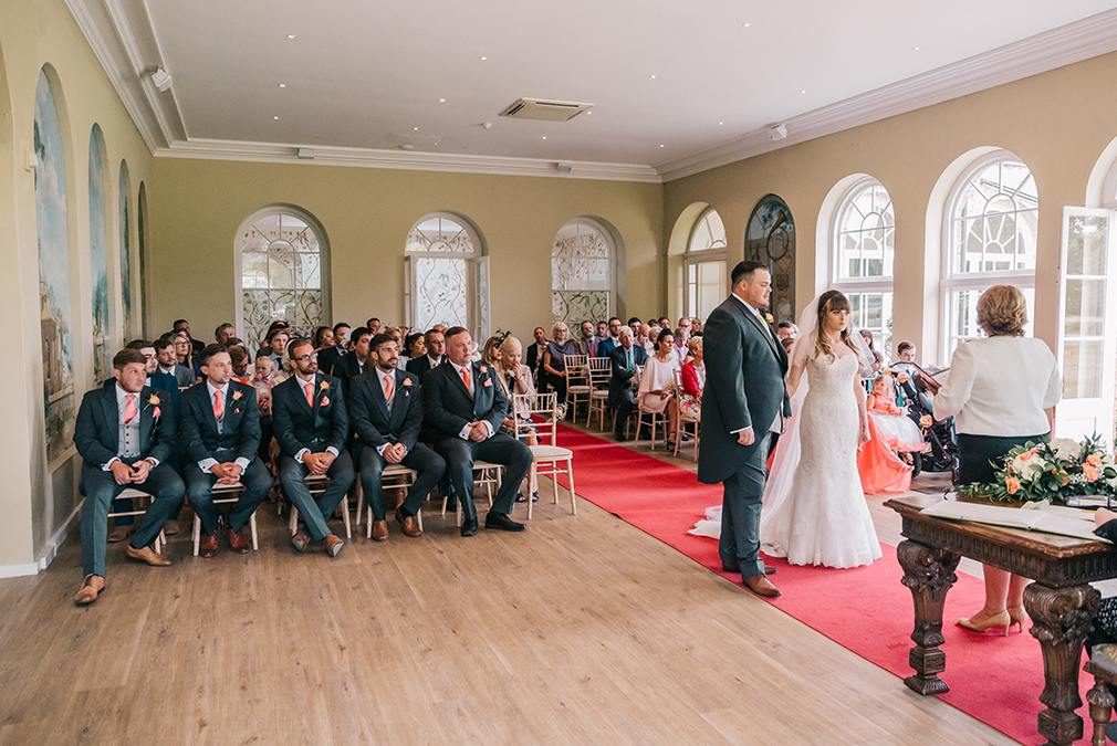 The bride and groom say their vows during a summer wedding ceremony in the Orangery at Braxted Park