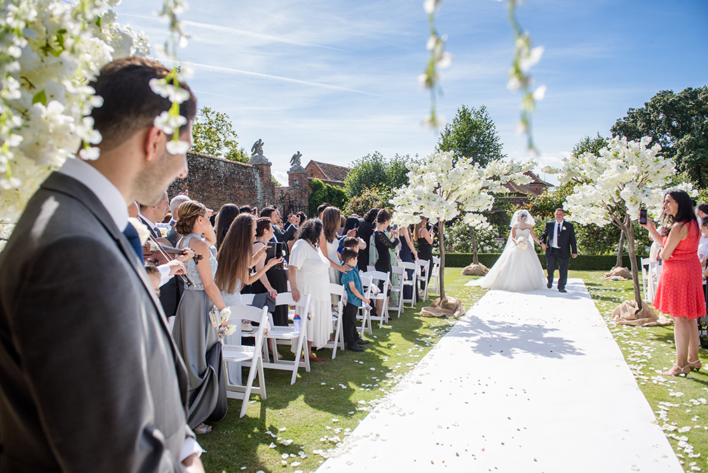 The bride walks down the aisle during her outdoor wedding ceremony in the gardens at Braxted Park in Essex