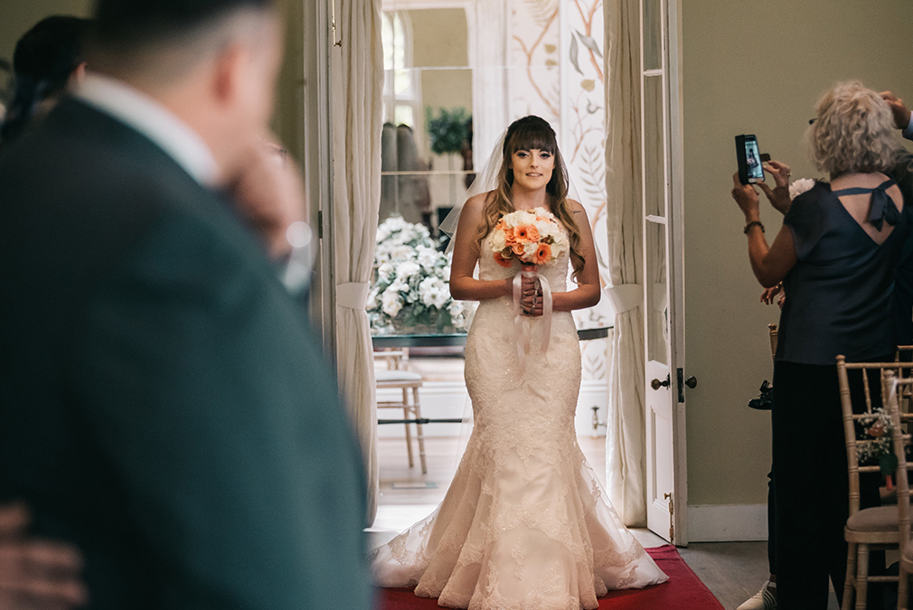 The bride walks down the aisle in the Orangery at Braxted Park during her wedding ceremony