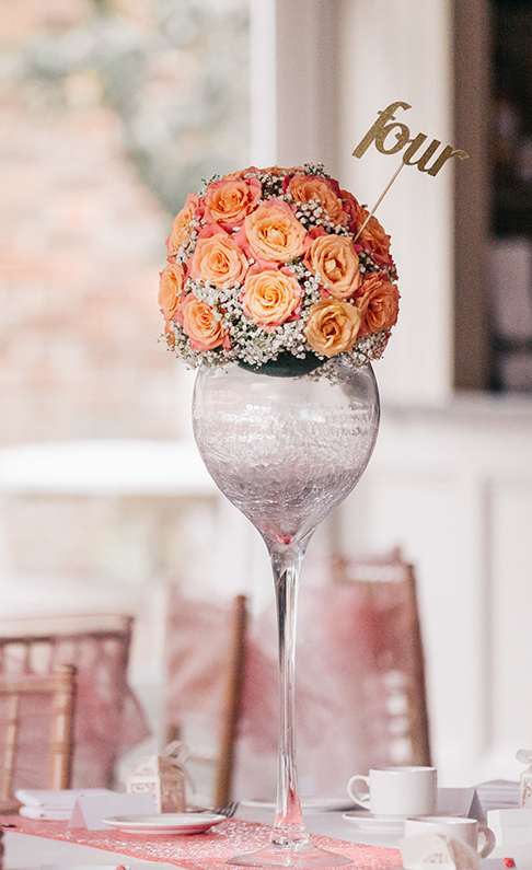 Wedding table centrepieces at Braxted Park are adorned with coral wedding flowers