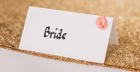 Name cards were decorated with coral flowers for this summer wedding at Braxted Park