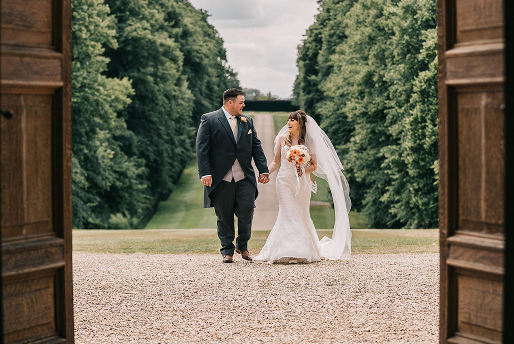 Newlyweds take a walk down the long driveway at Braxted Park on their summer wedding day