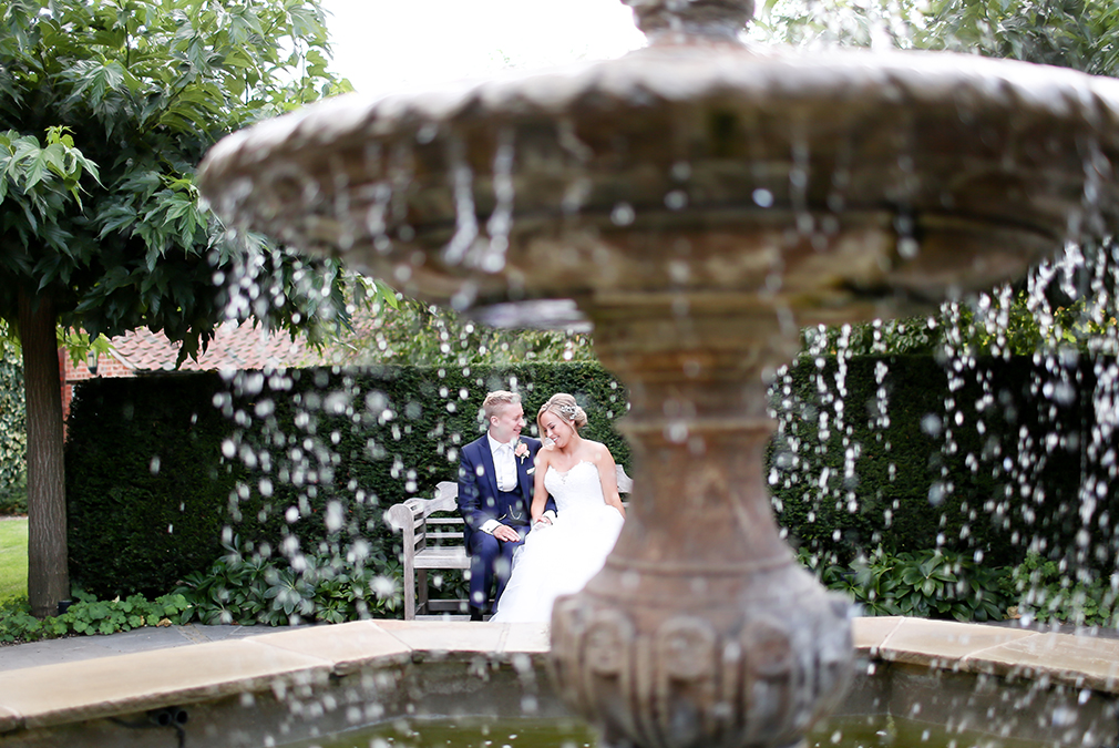 Newlyweds take a moment to explore the fountain and gardens at Braxted Park on their wedding day