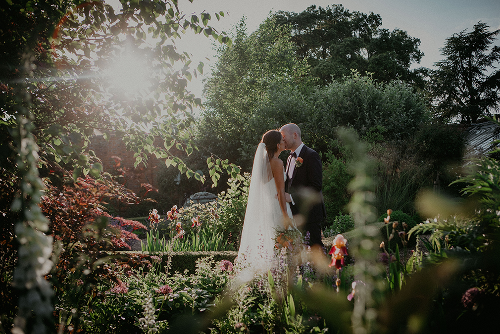 Newlyweds share a kiss in the Walled Gardens on their wedding day at Braxted Park in Essex
