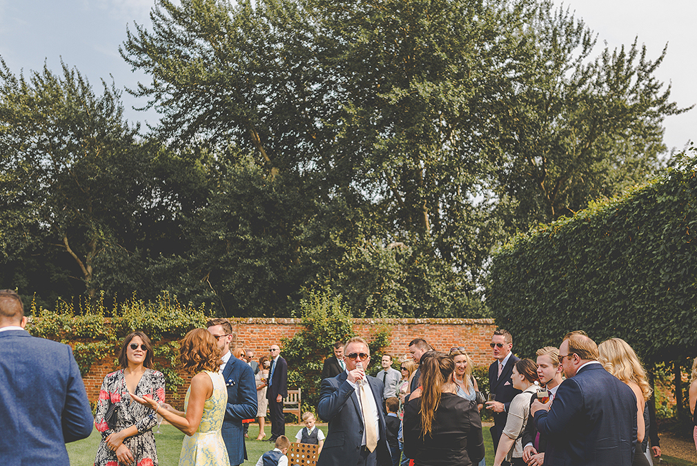 Wedding guests enjoy an outside drinks reception in the gardens at Braxted Park wedding venue in Essex