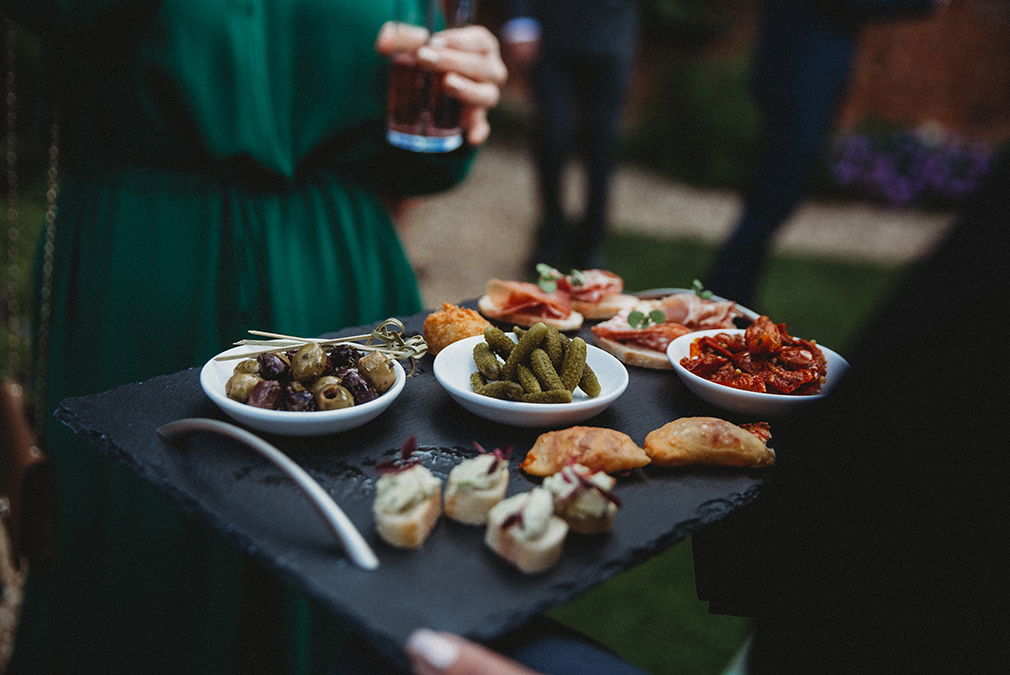 A selection of canapes are served to guests during an outdoor wedding drinks reception at Braxted Park