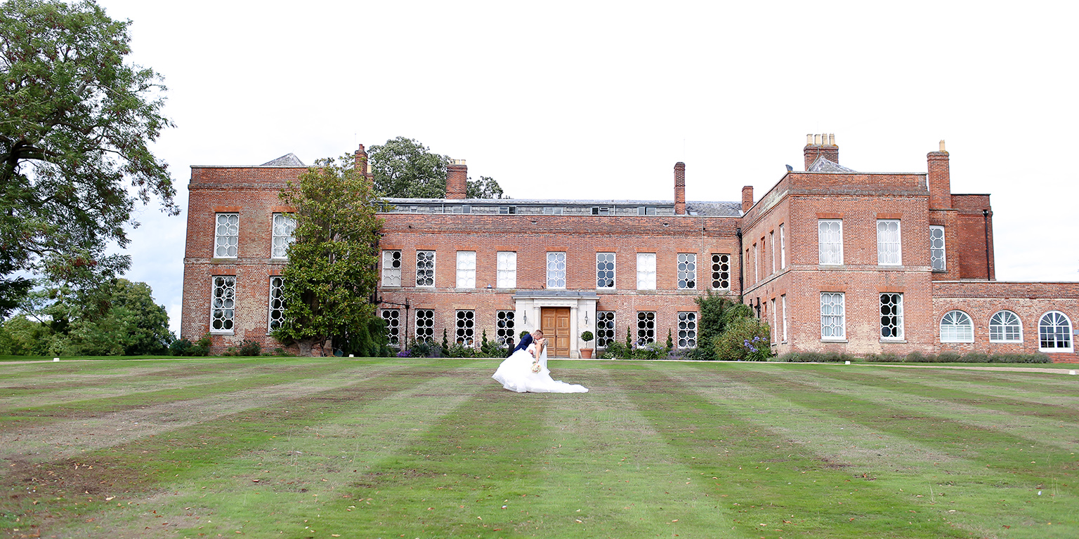 The bride and groom share a kiss on the lawns at Braxted Park on their wedding day