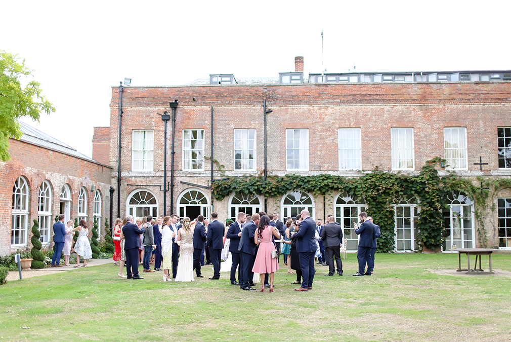 Guests enjoy an outdoor drinks reception on the lawns at Braxted Park