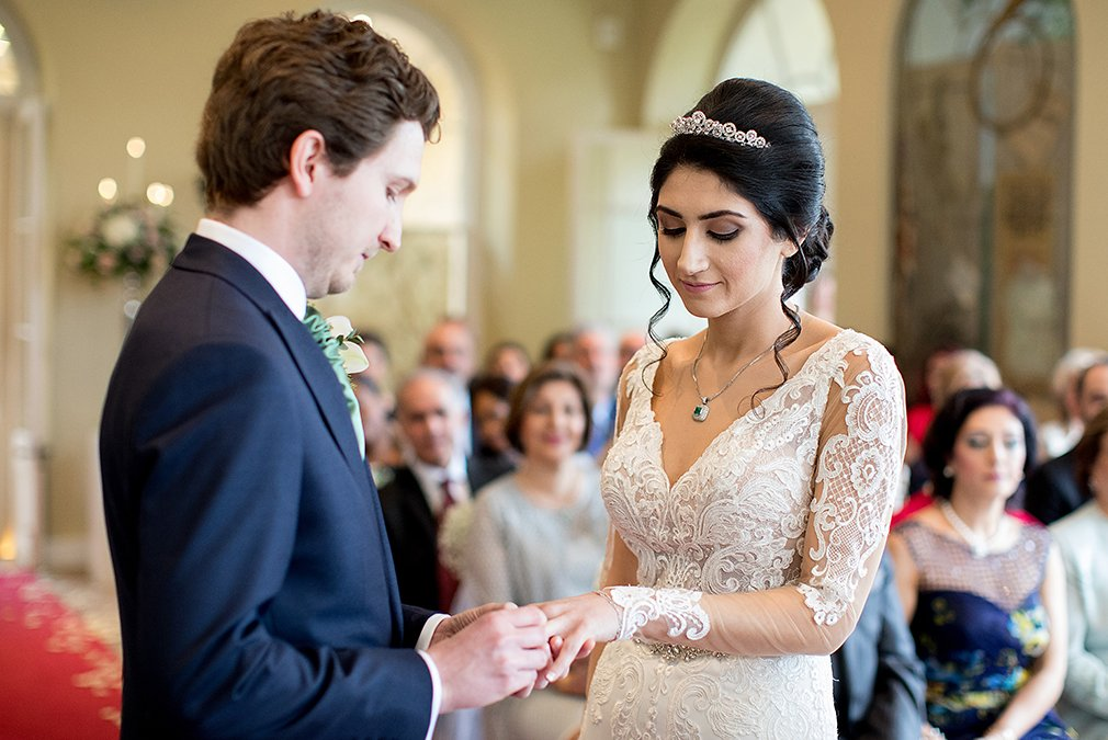 The bride and groom exchange rings during a wedding ceremony in The Orangery at Braxted Park