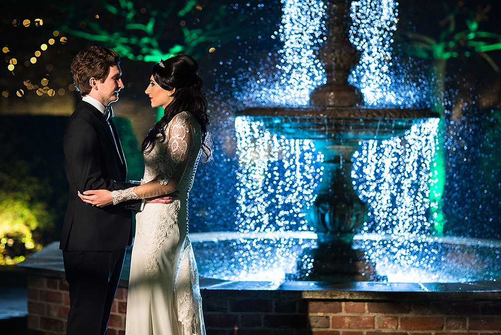 The couple stand in front of the fountain in the gardens at Braxted Park during their evening wedding reception