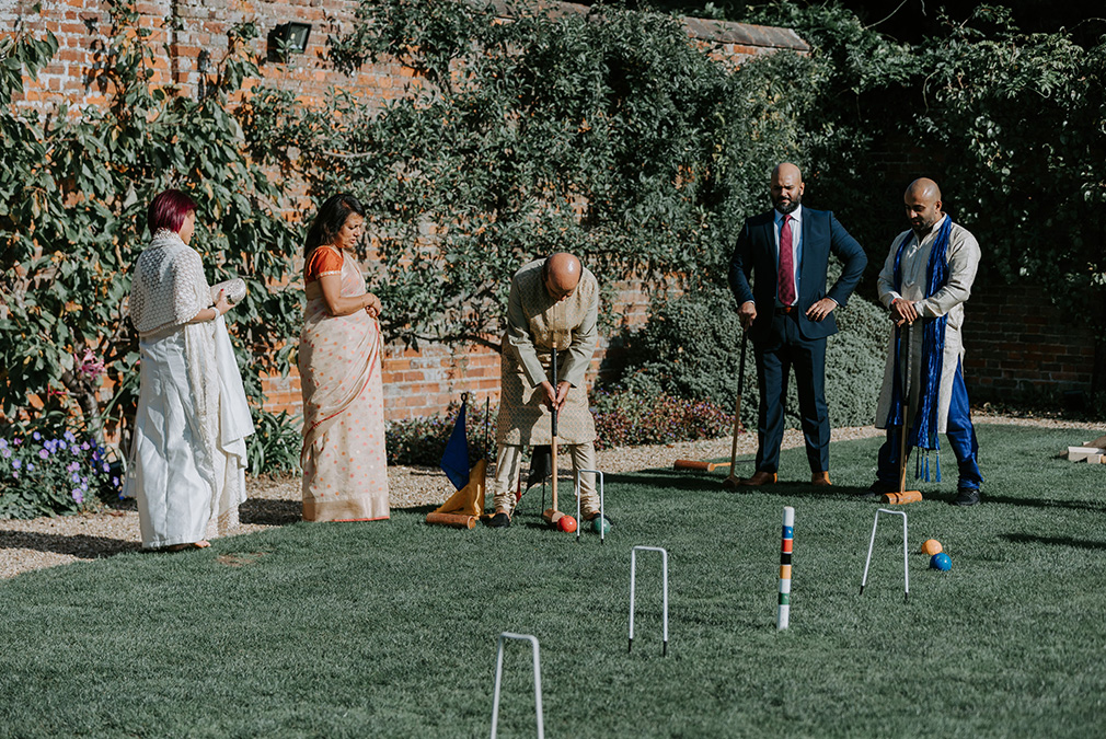 Wedding guests enjoy a game of croquet during an outdoor wedding reception at Braxted Park