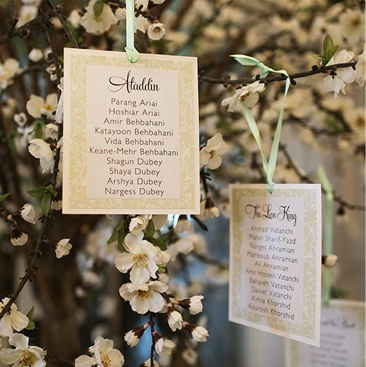 Table cards hang from a blossom tree to create an alternative wedding table plan at Braxted Park