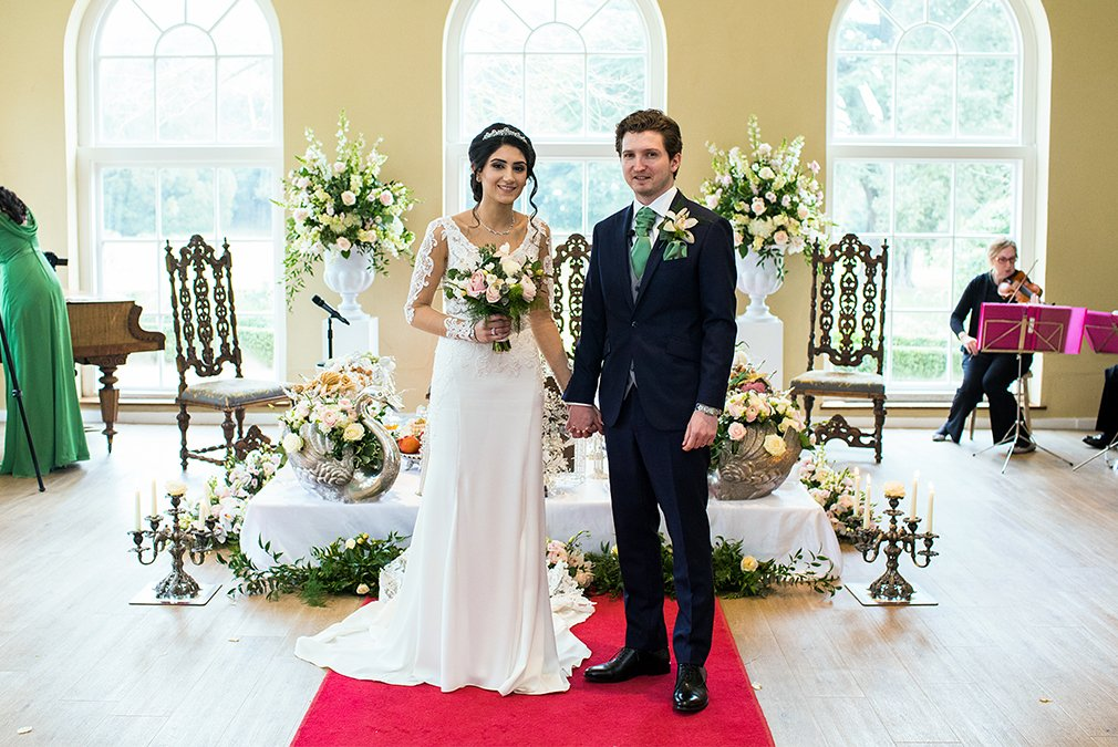 Newlyweds are surrounded by stunning wedding flowers in The Orangery at Braxted Park