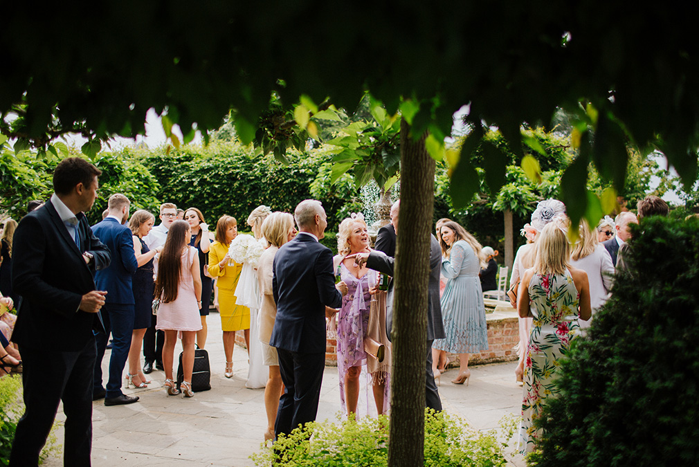 Wedding guests enjoy an outdoor drinks reception in the gardens at Braxted Park