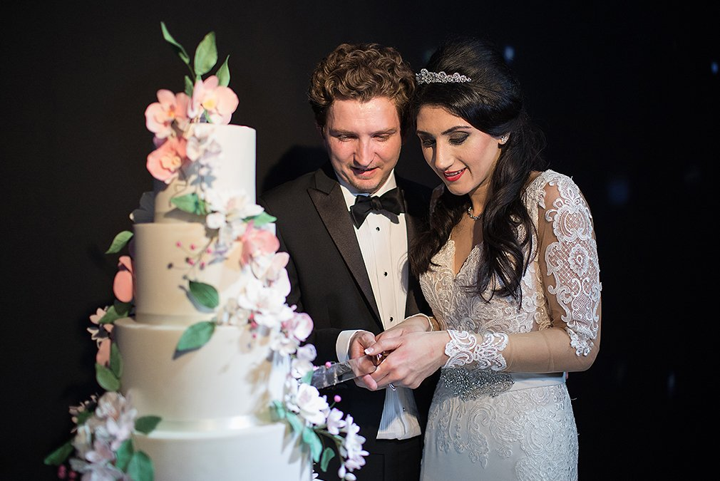The couple cut their wedding cake during the wedding reception at Braxted Park in Essex