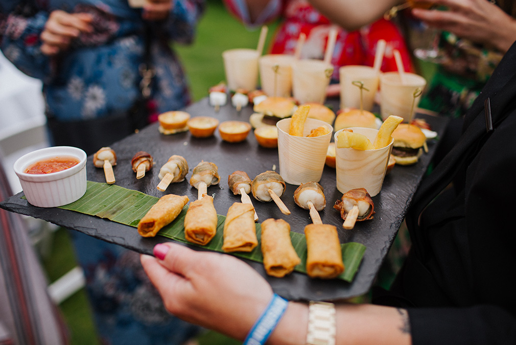 Wedding canapes are served in the gardens at Braxted Park during an outdoor drinks reception