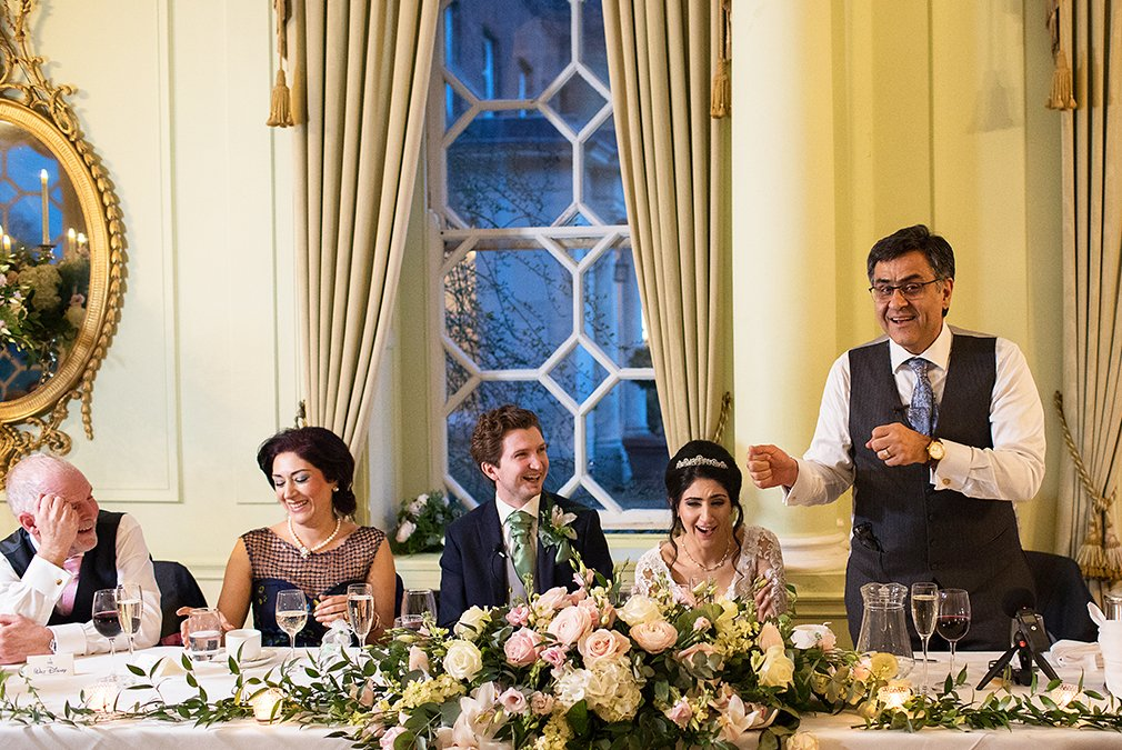 The newlyweds enjoy the father of the brides wedding speech in the Ballroom at Braxted Park