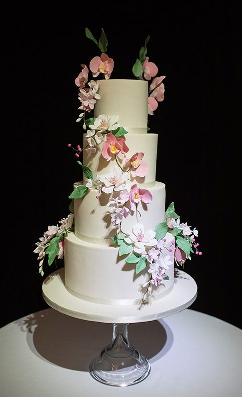 A white wedding cake is adorned with icing flowers for a wedding at Braxted Park